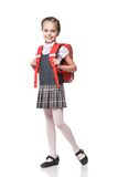 Cute smiling schoolgirl in uniform standing on Royalty Free Stock Photography