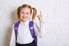 Cute smiling schoolgirl in uniform standing on light background and showing thumb up. Stock Image