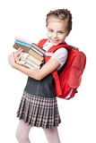 Cute smiling schoolgirl in uniform standing on Royalty Free Stock Photos