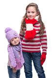 Cute smiling sisters wearing colorful knitted sweater, scarf, hat and gloves isolated on white background. Winter clothes. Stock Photography