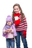 Cute smiling sisters wearing colorful knitted sweater, scarf, hat and gloves isolated on white background. Winter clothes. Royalty Free Stock Images