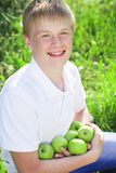 Cute smiling teen boy is holding green apples Royalty Free Stock Image