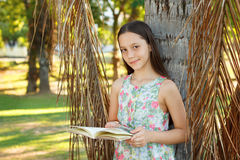 Cute smiling teen girl reading book. And looking to camera near palm tree, green grass in park. Selective focus stock photo