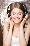 Cute smiling teenage girl in headphones listening Royalty Free Stock Photography