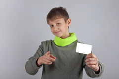 Cute smiling teenager holding white card and pointing towards you. Cute smiling teenager in sweatshirt holding white card and pointing towards you. Grey Royalty Free Stock Images