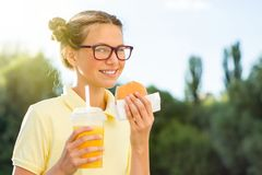 Cute smiling teenager in school uniform holding a hamburger and. Orange juice. Back to school Royalty Free Stock Photo