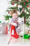 Cute smiling toddler girl checking her Christmas stocking Royalty Free Stock Image