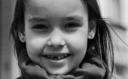 Cute smiling toothless girl looking at camera in black and white image stock images