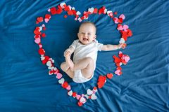 Caucasian baby girl boy infant with blue eyes four months old lying on bed among many colorful hearts