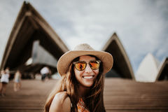Cute smiling woman close up portrait, with Sydney Opera House building in the background. Smiling girl in sunglasses visiting Sydney, with Opera House in the Stock Image