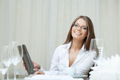 Cute smiling woman in glasses works on notebook Stock Photo