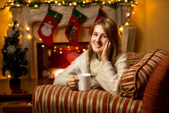Cute smiling woman holding cup of tea at fireplace Royalty Free Stock Photography