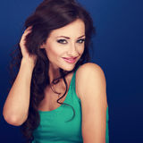 Cute smiling woman holding long curly brown hair and looking on Stock Image