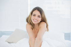 Cute smiling woman posing sitting on her bed Stock Photos