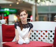 Cute smiling woman sitting inside in restaurant Royalty Free Stock Images