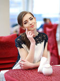 Cute smiling woman sitting inside in restaurant Stock Photos