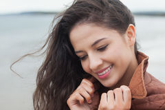 Cute smiling woman in stylish brown jacket on beach Stock Images