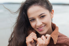 Cute smiling woman in stylish brown jacket on beach Stock Photos