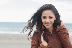 Cute smiling woman in stylish brown jacket on beach Royalty Free Stock Images