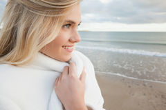 Cute smiling woman in stylish white jacket on beach Stock Image