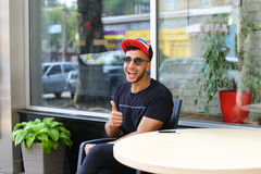 Cute smiling young arab holds thumb up and sitting in chair near Royalty Free Stock Photo