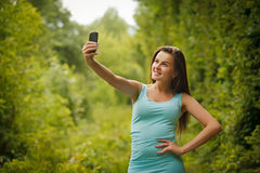 Cute smiling young Caucasian teenage girl taking a selfie outdoo Stock Image