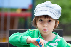 Cute smiling young child eating yogurt. Happy smiling young child eating yogurt, outdoor, making funny faces Stock Images