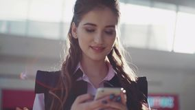 Cute smiling young woman with beautiful make-up in the pink shirt is in the shopping center. The girl browses Internet. Sunny day, good mood. Close up view stock footage