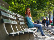 Cute smiling young woman in blue jacket sitting at bench, central park, New-York Royalty Free Stock Photography