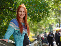 Cute smiling young woman in blue jacket standing near central park, New-York, close up Royalty Free Stock Images