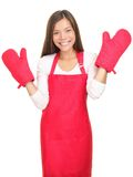 Cute smiling young woman with cooking mittens. Young woman with cooking mittens isolated on white background. Asian / Caucasian woman happy Royalty Free Stock Photography