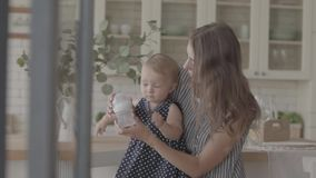 Cute smiling young woman feeding her baby girl with the bottle with baby`s dummy in the kitchen. Concept of a happy stock video