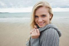 Cute smiling young woman in gray knitted jacket on beach Stock Image