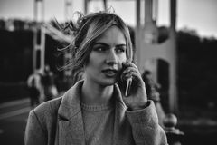 Cute smiling young woman talking on phone standing on the bride. stock photos
