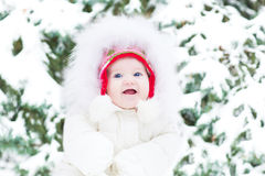 Cute smling baby girl in a warm white jacket sitting next to a C Royalty Free Stock Photography