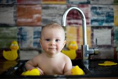 Cute snmiling baby taking bath in kitchen sink. Child playing wi stock photos
