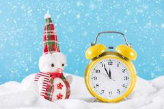 Snow man and retro clock on snow and it`s snowing at winter day royalty free stock photography