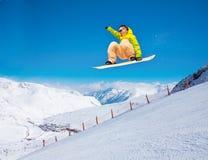 Cute snowboarder man jumping on ski resort Stock Photos