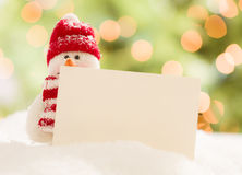 Cute Snowman with Blank White Card Over Abstract Background Stock Images