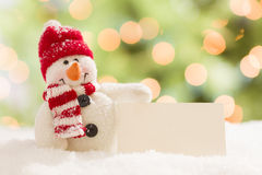 Cute Snowman with Blank White Card Over Abstract Background Royalty Free Stock Photography
