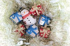 Cute snowman and christmas gifts box or presents on gold streamer or tinsel background Stock Images