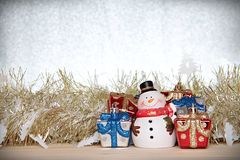Cute snowman, christmas gifts box or presents and gold streamer or tinsel on wood, silver glitter background Stock Photography