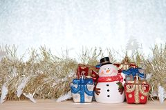 Cute snowman, christmas gifts box or presents and gold streamer or tinsel on wood, silver glitter background Stock Image