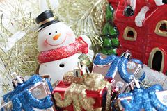 Cute snowman, christmas gifts box or presents and Santa Claus house on gold streamer or tinsel background Royalty Free Stock Image