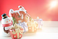 Cute snowman, christmas gifts box or presents and Santa Claus house on wood, red background Royalty Free Stock Photo