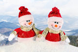 Two toy snowmen on a pile of snow with a mountain covered with snow in a background - Christmas postcard Stock Image