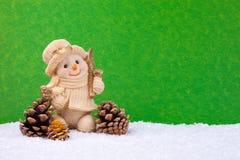 Cute snowman figure. Snowman figure in snow on green background Stock Photos
