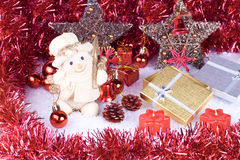 Cute snowman figure. On snow, xmas balls, candles and gifts Royalty Free Stock Images