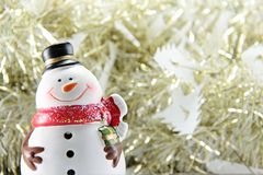 Cute snowman on gold streamer or tinsel background Royalty Free Stock Image