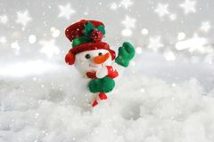 Cute snowman nestled in snow. Cute Christmas snowman waving nestled in snow Stock Image